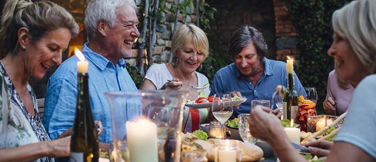 Skupina starších lidí sedící u stolu u společného jídla.
