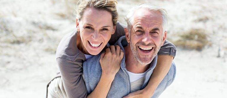 Starší muž kráčí po pláži a na zádech nese ženu.