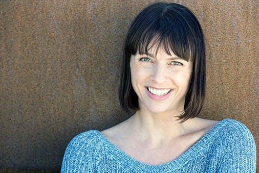 Frau steht lächelnd vor einer braunen Wand