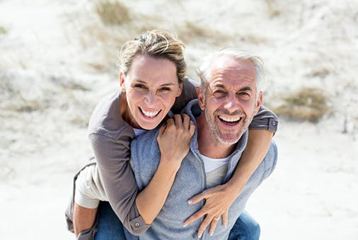 Älterer Mann mit Frau Huckepack am Strand.
