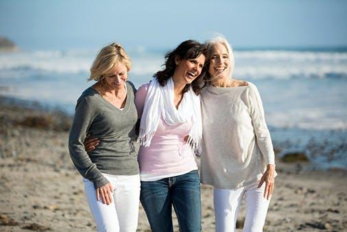 Drei ältere Frauen gehen am Strand spazieren.