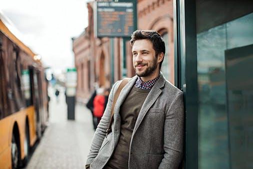 Mann mit Bart steht nonchalant an einer Bushaltestelle