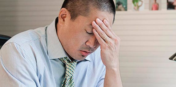 Stressed man holding his forehead.