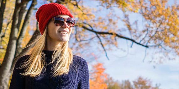 Young woman with hat and sunglasses in the park.
