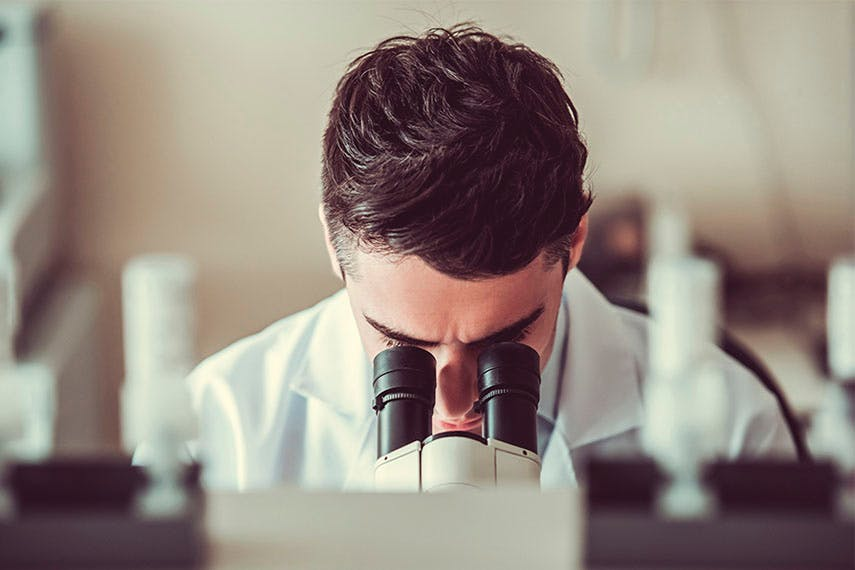 Man in a lab coat looking into a microscope