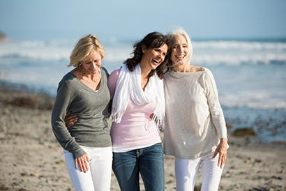 Three elderly ladies walking on the beach.