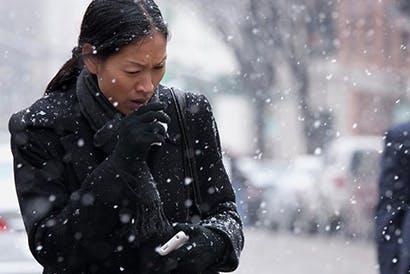 Coughing woman walking through falling snow.