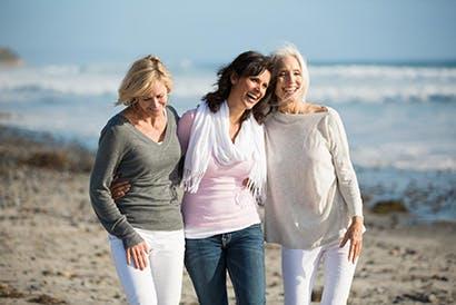 Három idősebb hölgy sétál a strandon.