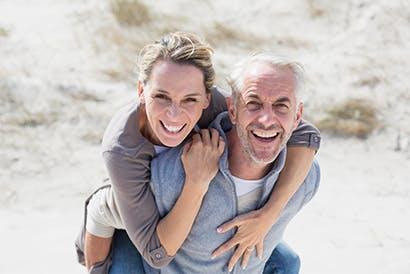 Egy idősebb férfi egy nőt visz a hátán a strandon.