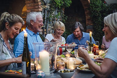 Egy idősebb emberekből álló csoport ül egy asztalnál, együtt étkeznek.