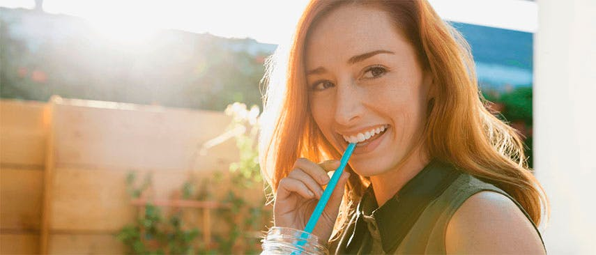 Woman smiling while drinking a juice