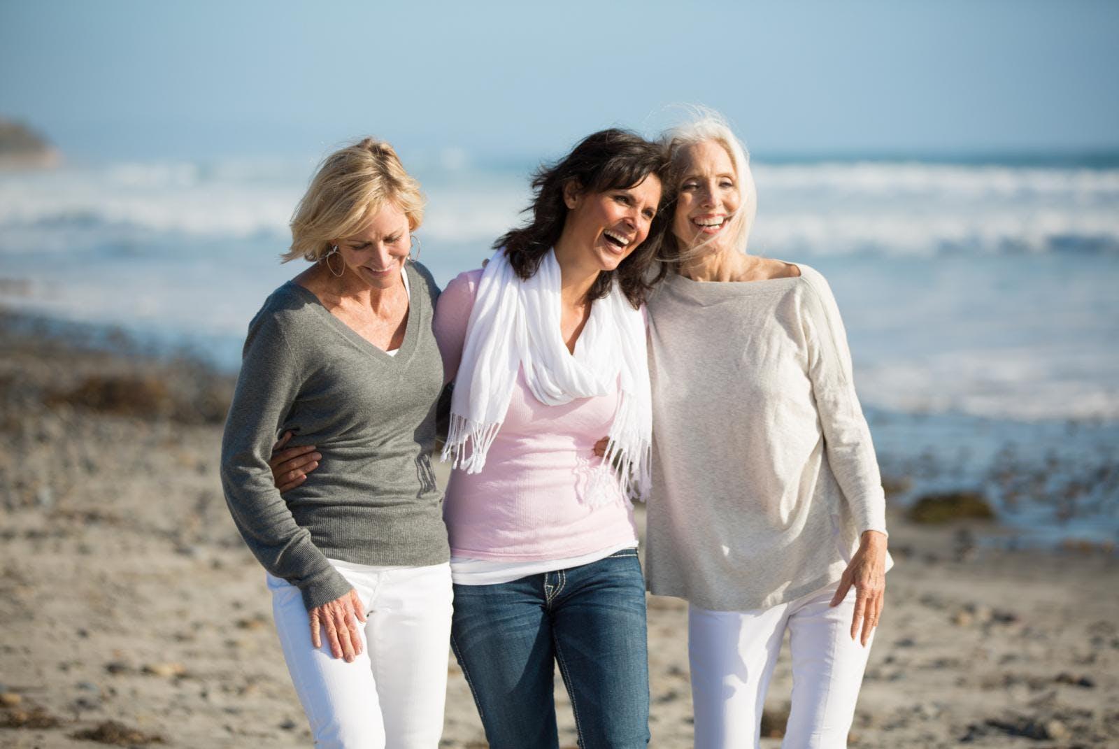 Drie oudere dames die over het strand lopen.