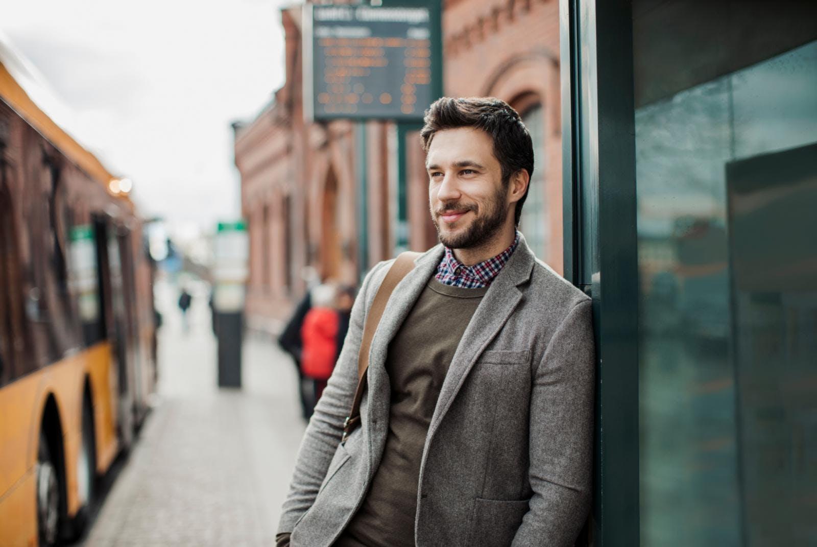 Man met een baard die achteloos bij een bushalte staat