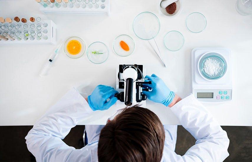 Kobieta prowadzaca badania w labolatorium za pomocą mikroskopu
