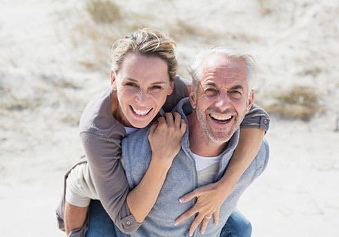 Homem idoso a levar uma mulher às cavalitas na praia.