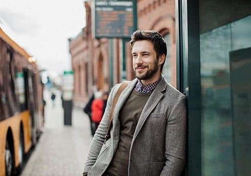 Homem de barba a aguardar serenamente numa paragem de autocarro