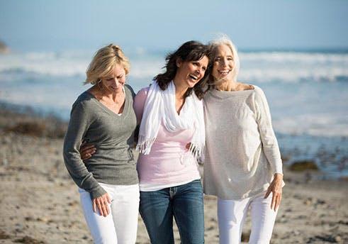 Três senhoras idosas a caminhar pela praia.