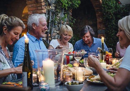 Grupo de pessoas idosas sentadas à mesa a comer.