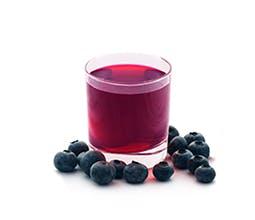 Glass of Sparkling Blueberry-Ginger Lemonade next to fresh blueberries