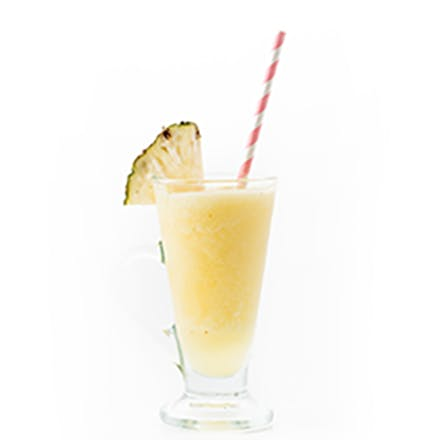 Tropical Medley Smoothie in glass with striped straw and pineapple wedge