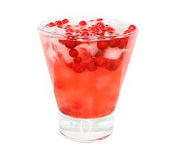 The Pominator festive red drink in glass with cranberries and ice cubes