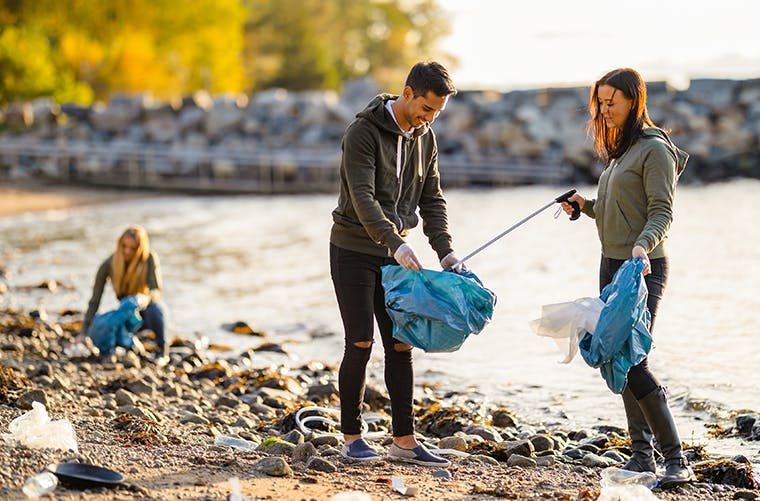 Man and woman picking up garbage on beach