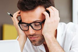 man in glasses holding his head