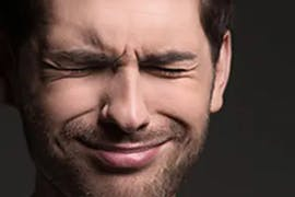 man squinting in pain
