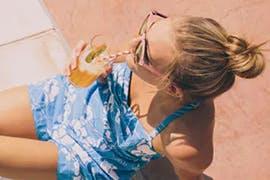 women in the sun drinking a drink