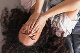 women laying on the floor with hands covering her face