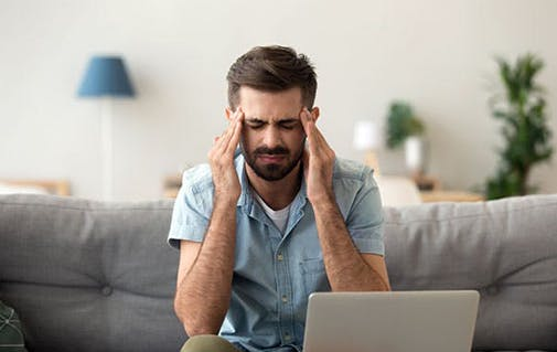 Man rubbing head with a headache