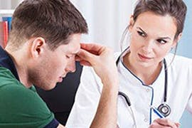 doctor talking to man with a headache
