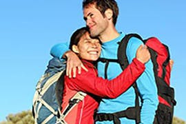 man and women with back packs cuddling