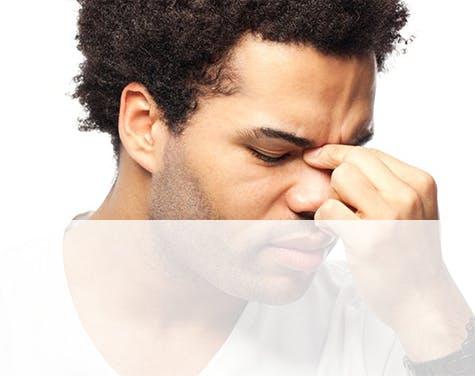 man touching his sinuses