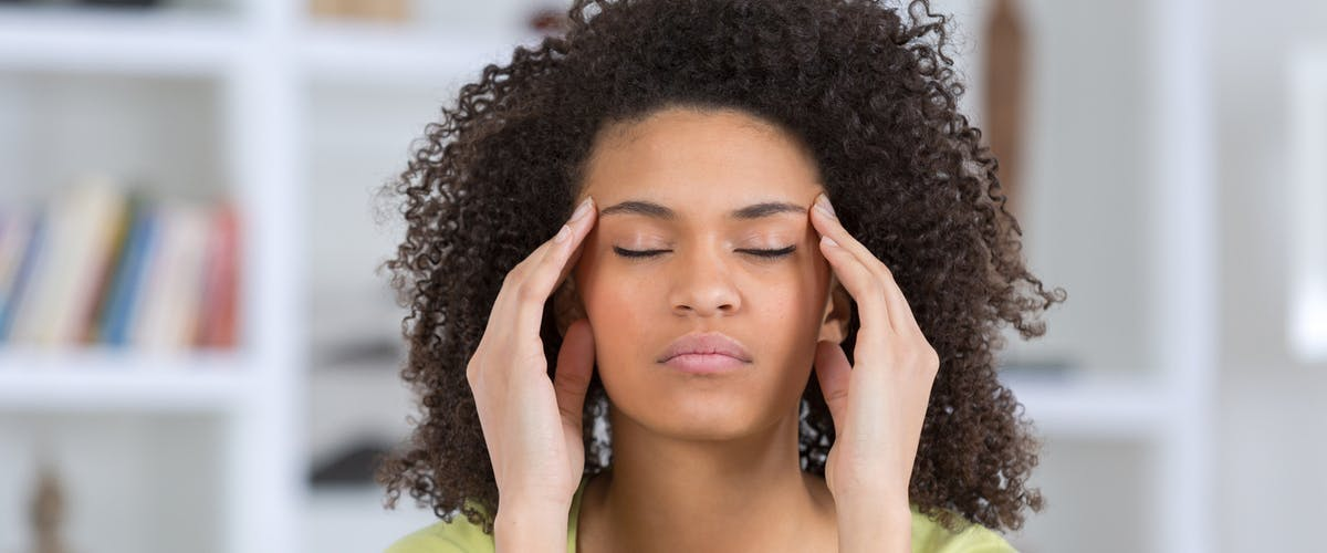 Young stressed woman with eyes closed and hands on her temples