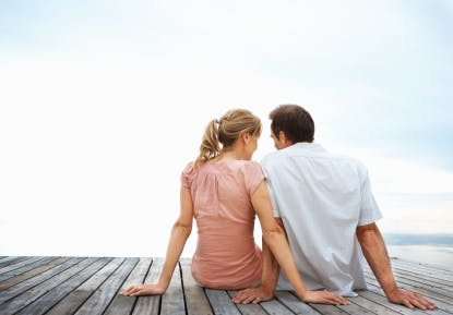 Couple sitting on a jetty with the sky as the background