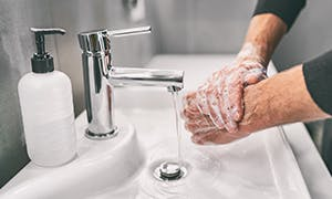 Person washing hands with soap