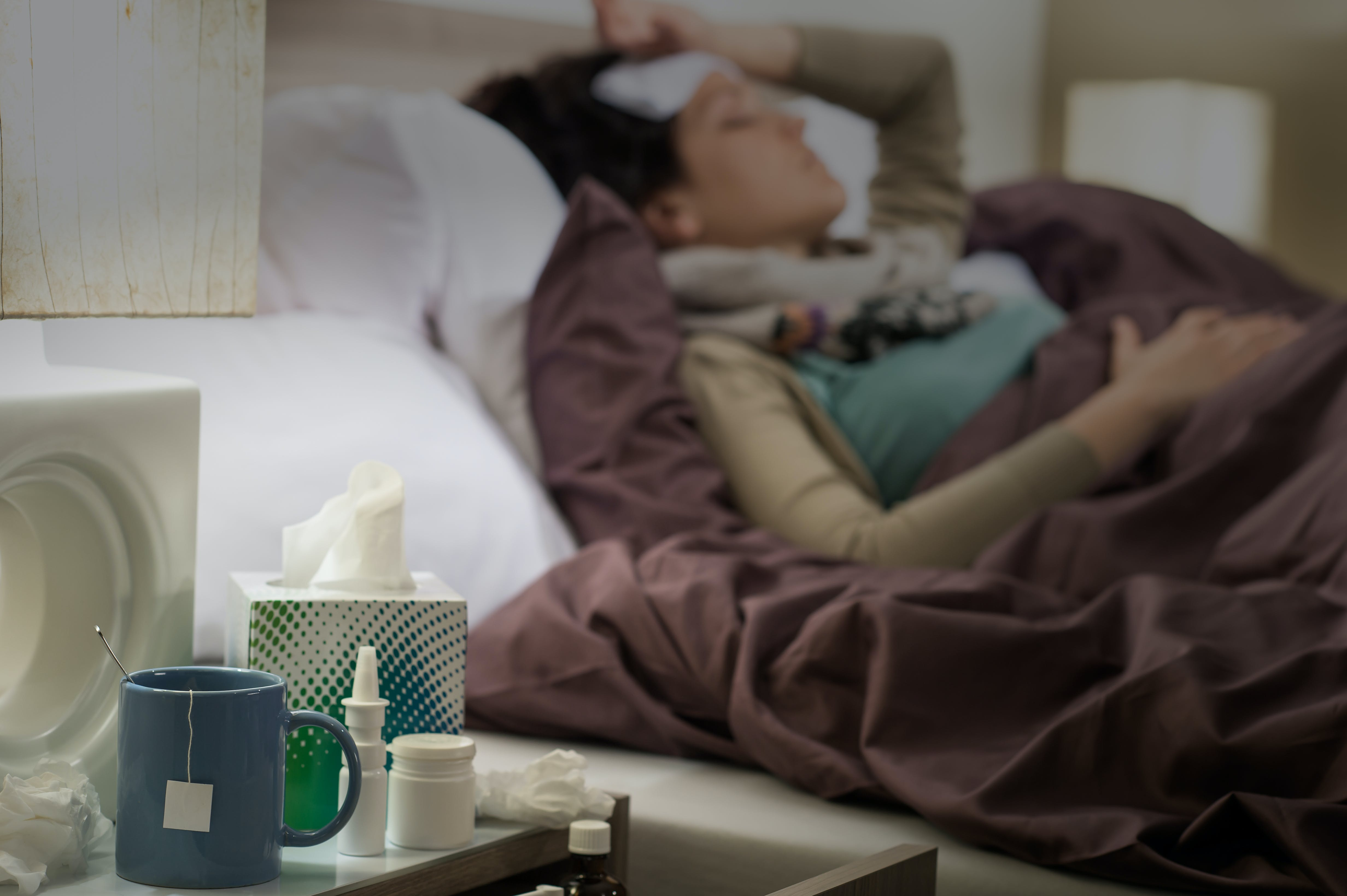 Woman lying in bed sick with flu medicines on the bedside table