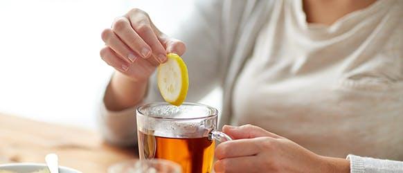 Women Dipping Lemon In Tea