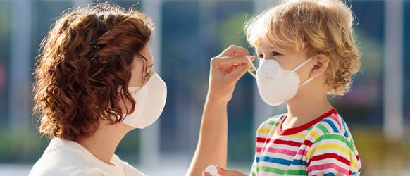 Mother helping child put on their face mask