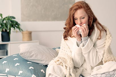 A woman is sitting up on bed, wrapped in a blanket and holding a tissue to her face