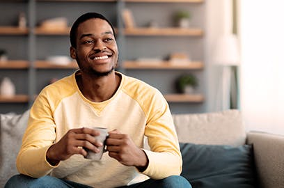A man is sitting on a sofa in the living room with a mug in his hand, he is smiling