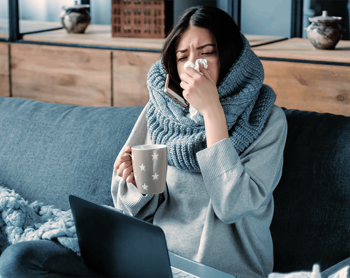 Sick woman wearing scarf blows nose on couch