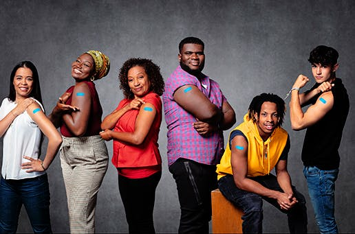 group of men and women showing their band aids and smiling