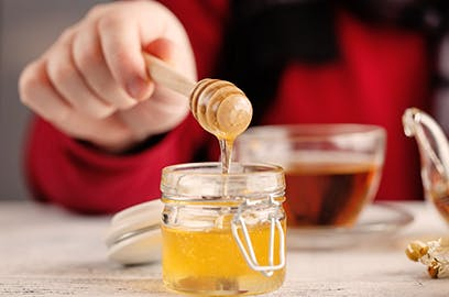 Hand dipping into honey with wooden stick, tea in background
