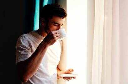 Man drinking cup of coffee next to a window