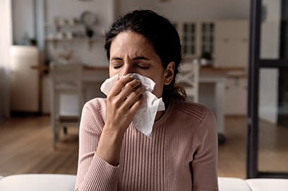 A lady is sneezing into a tissue
