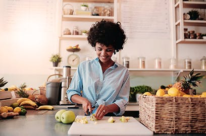 A woman standing in a kitchen is chopping apples on a board.