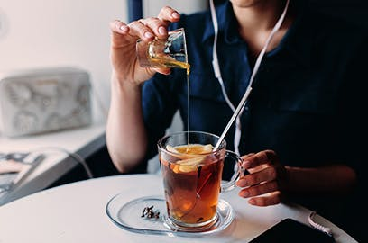 A person sitting at a table is pouring honey into hot tea with a lemon slice in it