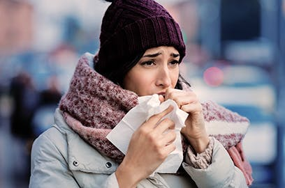 A woman is outside wearing a coat with a woolly hat and scarf holding a tissue to her face